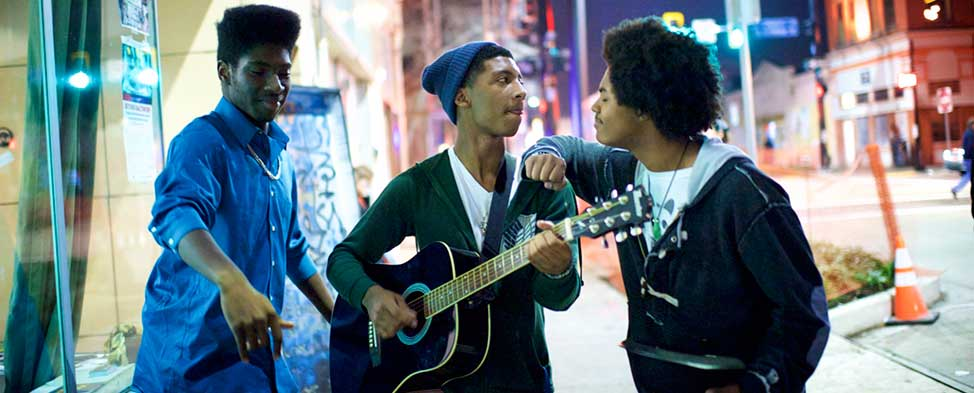 Three young men standing together outside on a city sidewalk singing and playing a guitar