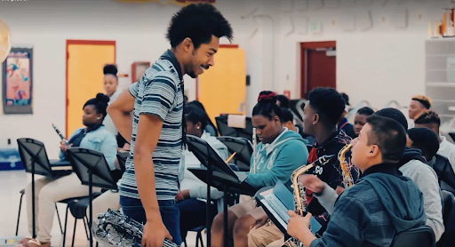 Two students of the Memphis Music Initiative talk during rehearsal